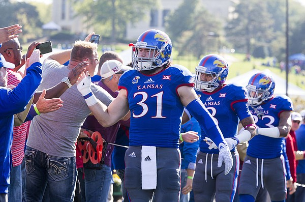 Kansas senior linebacker Ben Heeney (31) slaps hands with returning alumnus as he walks into the field before the start of Kansas' game against Oklahoma State on Saturday afternoon at Memorial Stadium.