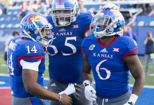 Kansas players Corey Avery (6), Mike Smithburg (65) and Michael Cummings (14) celebrate Avery's fourth quarter touchdown during their game against Oklahoma State Saturday afternoon at Memorial Stadium.