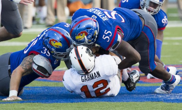Kansas senior buck Michael Reynolds (55) and junior lineman T.J. Semke team up to sack Oklahoma State quarterback Daxx Garman (12) during their game Saturday afternoon at Memorial Stadium.