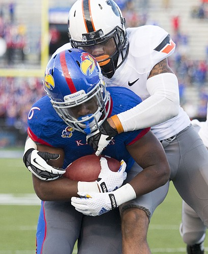 Kansas freshman running back Corey Avery is ridden out of bounds by Oklahoma State safety Jordan Sterns during their game Saturday afternoon at Memorial Stadium.