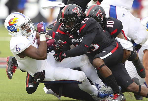 Kansas running back Corey Avery is dropped to the ground by Texas Tech defenders Jalen Barnes (19) and Pete Robertson (10) during the fourth quarter on Saturday, Oct. 18, 2014 at Jones AT&T Stadium in Lubbock, Texas.