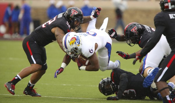 Kansas running back Corey Avery is taken off his feet by several Texas Tech defenders during the first quarter on Saturday, Oct. 18, 2014 at Jones AT&T Stadium in Lubbock, Texas.