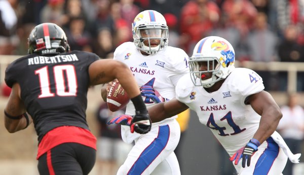 Kansas quarterback Michael Cummings looks to throw as Texas Tech linebacker Pete Robertson is fended off by KU tight end Jimmay Mundine during the second quarter on Saturday, Oct. 18, 2014 at Jones AT&T Stadium in Lubbock, Texas.