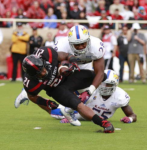 Kansas defenders Courtney Arnick (28) and Michael Reynolds (55) try to bring down Texas Tech running back DeAndre Washington during the third quarter on Saturday, Oct. 18, 2014 at Jones AT&T Stadium in Lubbock, Texas.