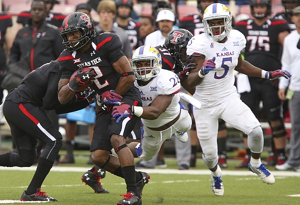 Kansas linebacker Courtney Arnick dives to wrap up Texas Tech receiver Reginald Davis during the third quarter on Saturday, Oct. 18, 2014 at Jones AT&T Stadium in Lubbock, Texas. At right is Kansas safety Isaiah Johnson.