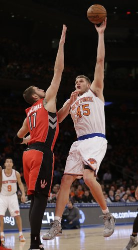 New York Knicks' Cole Aldrich (45) shoots over Toronto Raptors' Jonas Valanciunas (17) during the first half of an NBA basketball game Wednesday, April 16, 2014, in New York. (AP Photo/Frank Franklin II)