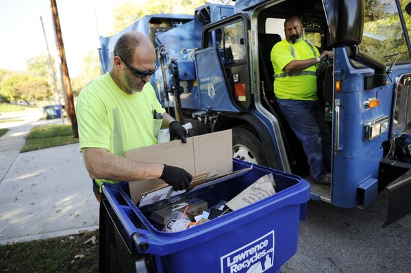 Lawrence public works employee Duane LaFrenz, left, conducts quality control as driver Mike Brown waits to pick up a load of recycling, Tuesday, Oct. 21, 2014, in north Lawrence.