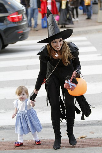 In this file photo, Jordan Noller assists her 13-month-old daughter Scotlyn across the street during the 2013 Downtown Lawrence Halloween Trick-or-Treat.