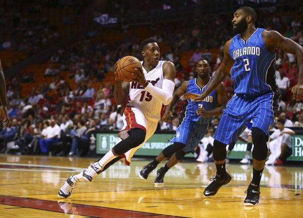 Miami Heat's Mario Chalmers (15) drives around Orlando Magic'sKyle O'Quinn (2) during the first half of a NBA basketball game in Miami, Oct. 7, 2014. (AP Photo/J Pat Carter)