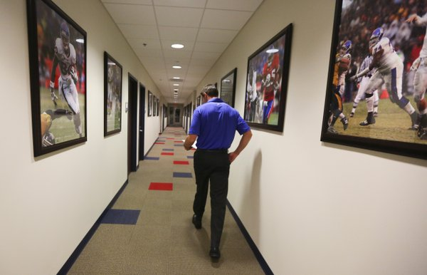 Shortly after 6:30 a.m., Kansas interim head football coach Clint Bowen walks toward his office down a hallway lined with rows of images documenting the high points from the program's recent history, Wednesday, Oct. 22, 2014.