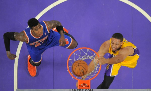Los Angeles Lakers forward Xavier Henry, right, dunks as New York Knicks guard Iman Shumpert defends during the first half of an NBA basketball game, Tuesday, March 25, 2014, in Los Angeles. (AP Photo/Mark J. Terrill)