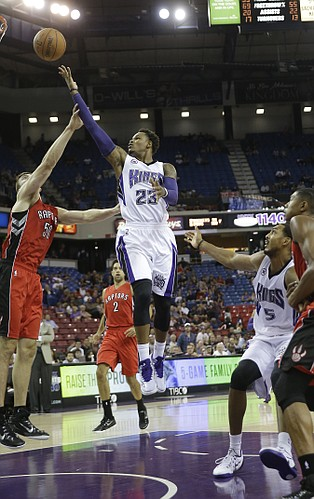Sacramento Kings guard Ben McLemore, right, drives to the basket against Toronto Raptors forward Tyler Hansbrough, left, during the fourth quarter of an NBA preseason basketball game in Sacramento, Calif., Tuesday, Oct. 7, 2014. The Kings won 113-106. (AP Photo/Rich Pedroncelli)