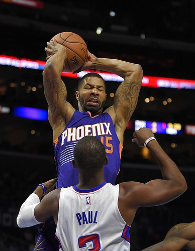 Phoenix Suns forward Marcus Morris, top, grabs a rebound away from Los Angeles Clippers guard Chris Paul during the first half of a preseason NBA basketball game, Wednesday, Oct. 22, 2014, in Los Angeles. (AP Photo/Mark J. Terrill)