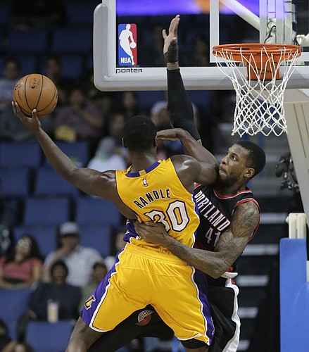 Los Angeles Lakers' Julius Randle, left, goes up for a shot against Portland Trail Blazers' Thomas Robinson during the second half of a preseason NBA basketball game Wednesday, Oct. 22, 2014, in Ontario, Calif. The Lakers won 94-86. (AP Photo/Jae C. Hong)