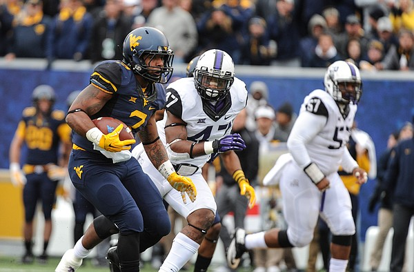 West Virginia's Rushel Shell (7) runs by the TCU defense during the first quarter of an NCAA college football game in Morgantown, W.Va., Saturday, Nov. 1, 2014. (AP Phpto/Tyler Evert)