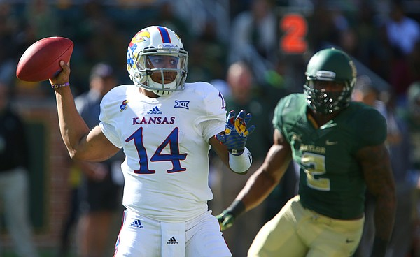 Kansas quarterback Michael Cummings turns to throw as Baylor defensive end Shawn Oakman closes in during the first quarter at McLane Stadium on Saturday, Nov. 1, 2014 in Waco, Texas.
