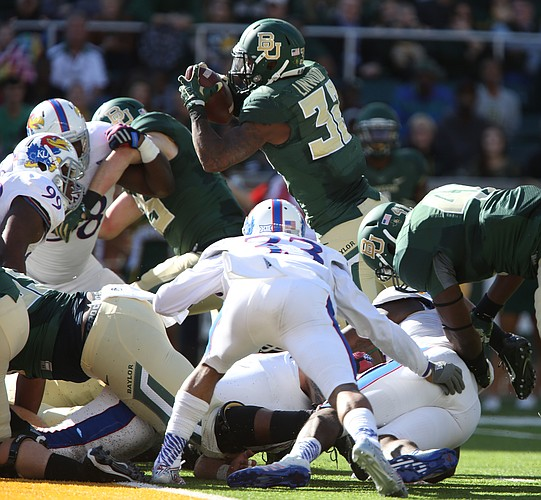 Baylor running back Shock Linwood leaps over the pile toward the end zone for a touchdown during the first quarter at McLane Stadium on Saturday, Nov. 1, 2014 in Waco, Texas.