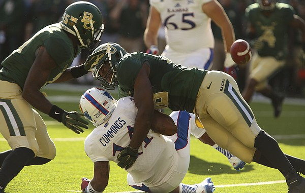 Kansas quarterback Michael Cummings fumbles the ball after being hit by Baylor defensive end K.J. Smith during the second quarter at McLane Stadium on Saturday, Nov. 1, 2014 in Waco, Texas. The Bears recovered the ball.