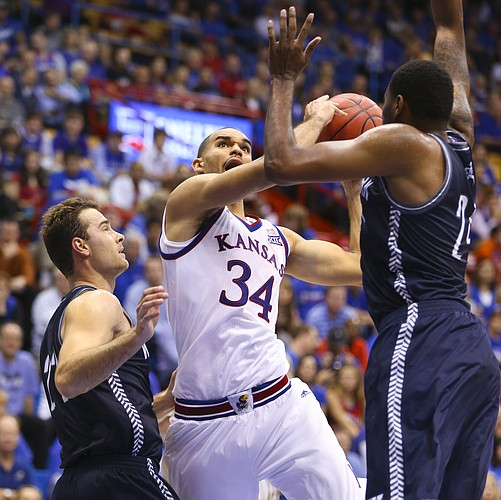 Kansas forward Perry Ellis heads to the bucket between Washburn defenders Alex North, left, and Stephon Drane during the second half on Monday, Nov. 3, 2014 at Allen Fieldhouse.