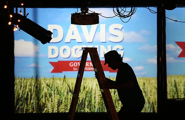 Josh Erbmann, a video support worker comes down from a ladder while preparing for a watch party for democratic gubernatorial candidate Paul Davis on Tuesday, Nov. 4, 2014 at Abe & Jake's Landing in Lawrence.