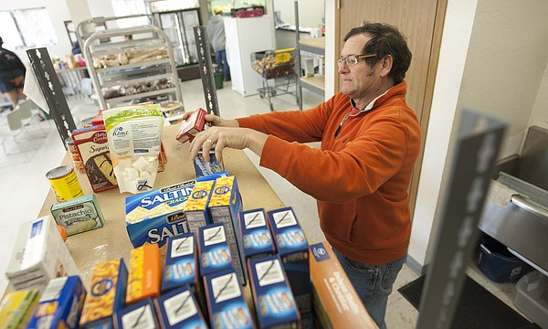 Davis Loupe, a volunteer at Just Food at 1000 E. 11th St., stocks shelves at the food bank on Nov. 6, 2014.