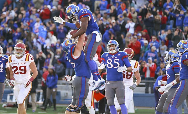 Kansas offensive lineman Mike Smithburg hoists up tight end Jimmay Mundine after Mundine's touchdown against Iowa State during the first quarter on Saturday, Nov. 8, 2014.