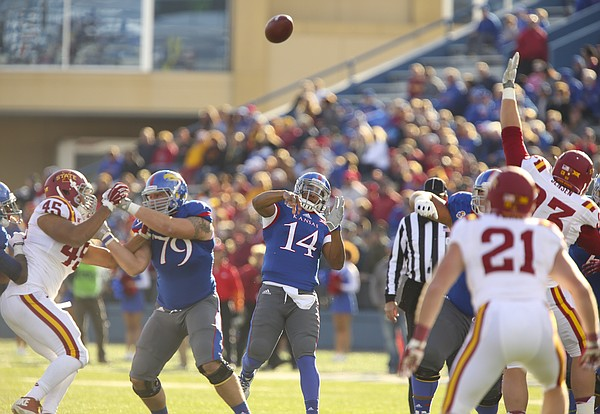 Kansas quarterback Michael Cummings heaves a pass over the Iowa State defense during the first quarter on Saturday, Nov. 8, 2014.