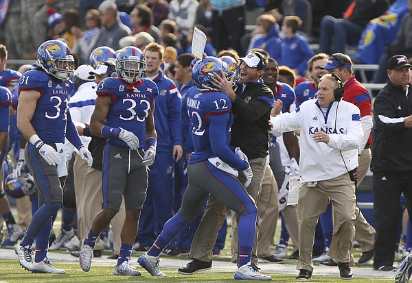 Kansas interim head coach Clint Bowen celebrates a defensive stop with cornerback Dexter McDonald against Iowa State during the first quarter on Saturday, Nov. 8, 2014.