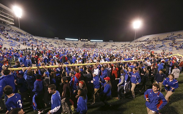 Kansas University football fans march with and upright to Potter Lake following the Jayhawks' 34-14 win over the Cyclones on Saturday, Nov. 8, 2014.