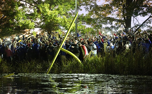 Kansas football fans toss part of an upright into Potter Lake following the Jayhawks' 34-14 win over the Cyclones on Saturday, Nov. 8, 2014.