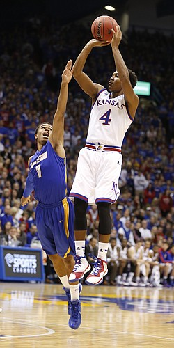 Kansas guard Devonte Graham pulls up for a jumper past UC Santa Barbara guard Eric Childress during the first half on Friday, Nov. 14, 2014 at Allen Fieldhouse.