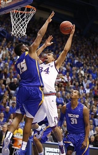 Kansas forward Perry Ellis goes to the bucket against UC Santa Barbara forward Alan Williams during the first half on Friday, Nov. 14, 2014 at Allen Fieldhouse. At right is UCSB guard John Green.