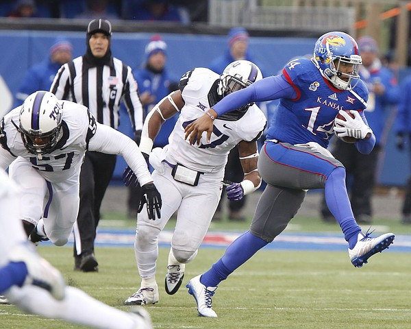 Kansas quarterback Michael Cummings breaks away from TCU defenders Davion Pierson (57) and Paul Dawson (47) during the first quarter on Saturday, Nov. 15, 2014 at Memorial Stadium.