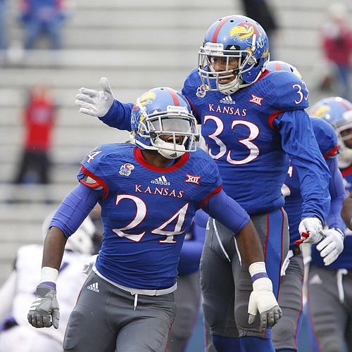 Kansas players JaCorey Shepherd (24) and Cassius Sendish celebrate Shepherd's interception of TCU quarterback Trevone Boykin during the second quarter on Saturday, Nov. 15, 2014 at Memorial Stadium.