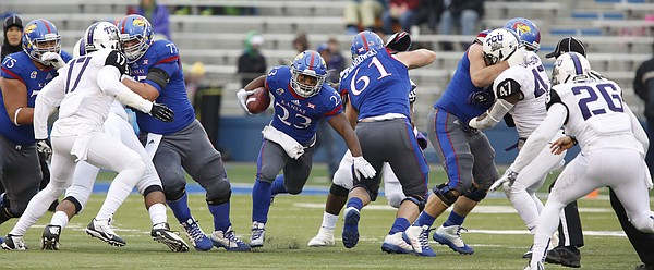 Kansas running back DeAndre Mann finds a hole up the middle against TCU during the second quarter on Saturday, Nov. 15, 2014 at Memorial Stadium.