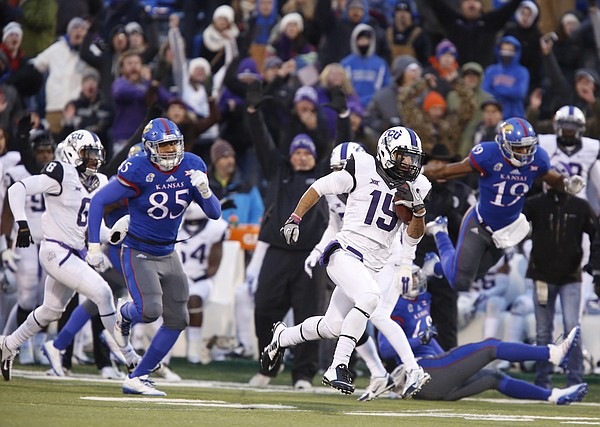 TCU return man Cameron Echols-Luper runs back a punt for a touchdown and the lead as he is tailed by Kansas special teams player Trent Smiley during the third quarter on Saturday, Nov. 15, 2014 at Memorial Stadium.