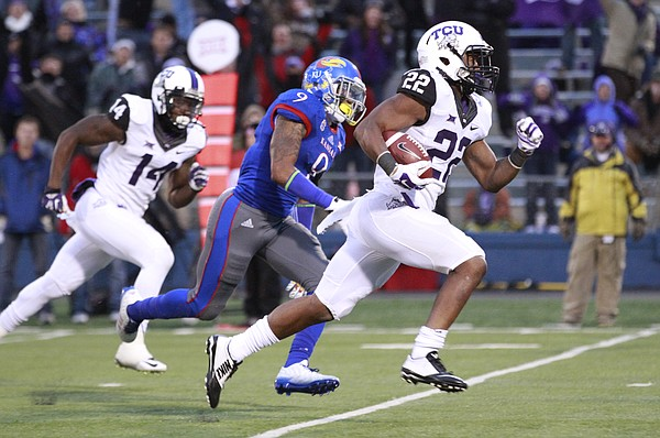 TCU running back Aaron Green races past Kansas safety Fish Smithson for a touchdown during the third quarter on Saturday, Nov. 15, 2014 at Memorial Stadium.