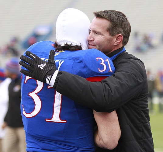 Kansas interim head coach Clint Bowen gives a big hug to senior linebacker Ben Heeney as Heeney is introduced with the rest of the seniors prior to kickoff on Saturday, Nov. 15, 2014 at Memorial Stadium.