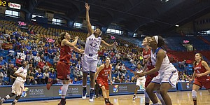 Kansas senior guard Natalie Knight (42) gets loose inside the lane to score an easy two points in front of South Dakota junior guard Kelly Stewart (15) during the second half of their game Sunday afternoon at Allen Fieldhouse. The Jayhawks held off the Coyotes, 68-60, for a season opening victory.