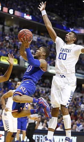 Kansas guard Frank Mason III (0) elevates to the bucket under the outstretched arm of Kentucky forward Marcus Lee (00) during the first half of the Champions Classic on Tuesday, Nov. 18, 2014 at Bankers Life Fieldhouse in Indianapolis.