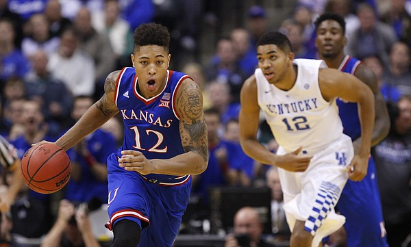 Kansas guard Kelly Oubre Jr. (12) pushes the ball up the court against Kentucky during the first half of the Champions Classic on Tuesday, Nov. 18, 2014 at Bankers Life Fieldhouse in Indianapolis.