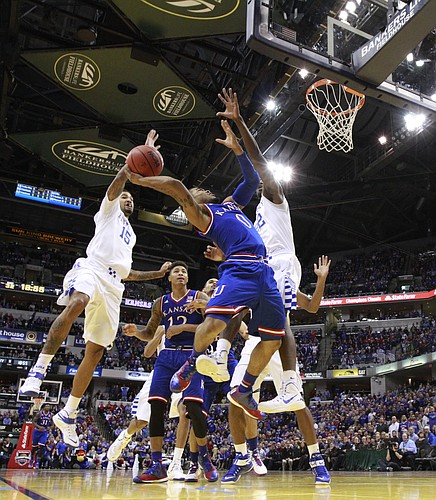 Kansas guard Frank Mason III (0) has his shot blocked by Kentucky forward Willie Cauley-Stein (15) during the second half of the Champions Classic on Tuesday, Nov. 18, 2014 at Bankers Life Fieldhouse in Indianapolis. Also pictured are Kansas guard Kelly Oubre Jr. (12) and Kentucky forward Alex Poythress (22).