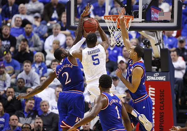 Kentucky guard Andrew Harrison (5) gets to the bucket between Kansas forward Cliff Alexander (2) and forward Perry Ellis (34) during the second half of the Champions Classic on Tuesday, Nov. 18, 2014 at Bankers Life Fieldhouse in Indianapolis.