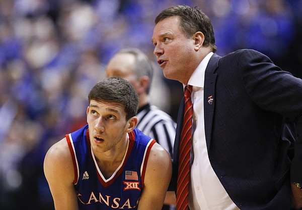 Kansas guard Sviatoslav Mykhailiuk leans down for a talk with head coach Bill Self during the second half of the Champions Classic on Tuesday, Nov. 18, 2014 at Bankers Life Fieldhouse in Indianapolis.