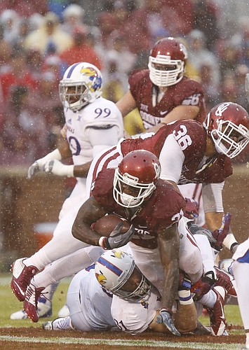 Oklahoma running back Keith Ford (21) dives over Kansas linebacker Ben Heeney (31) for yardage during the first quarter on Saturday, Nov. 22, 2014 at Memorial Stadium in Norman, Oklahoma. Above is OU fullback Dimitri Flowers (36).