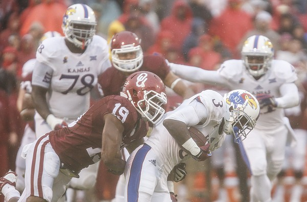 Kansas wide running back Tony Pierson (3) is dragged down by Oklahoma linebacker Eric Striker (19) during the quarter on Saturday, Nov. 22, 2014 at Memorial Stadium in Norman, Oklahoma.