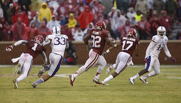 Oklahoma running back Samaje Perine (32) has blockers as he heads up the field against the Kansas defense during the third quarter on Saturday, Nov. 22, 2014 at Memorial Stadium in Norman, Oklahoma.