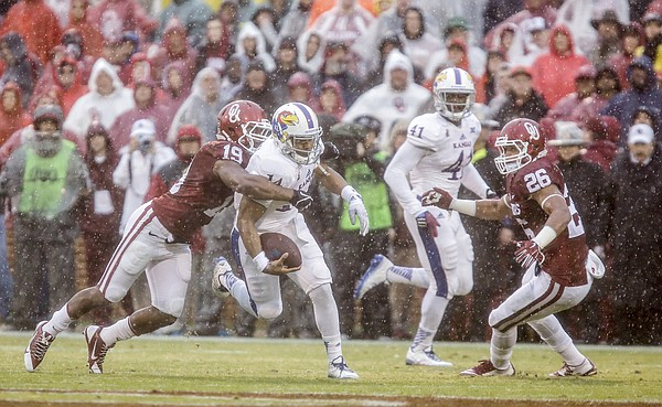 Kansas quarterback Michael Cummings is dragged down short of a first down by Oklahoma linebacker Eric Striker (19) during the first quarter on Saturday, Nov. 22, 2014 at Memorial Stadium in Norman, Oklahoma. At right is Oklahoma linebacker Jordan Evans (26).