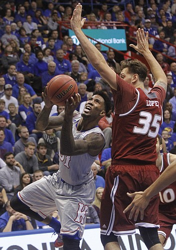 Kansas junior forward Jamari Traylor shoots under Rider center Mat Lopez in the Jayhawks 87-60 win over the Broncs Monday night at Allen Fieldhouse.