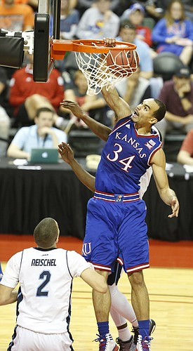 Kansas forward Perry Ellis (34) delivers a put-back dunk over Rhode Island forward Jarelle Reischel (2) during the first half on Thursday, Nov. 27, 2014 at the HP Field House in Kissimmee, Florida.